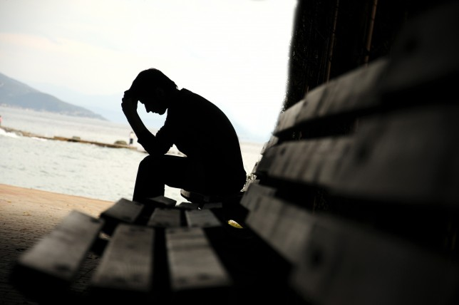depressed young man sitting on the bench