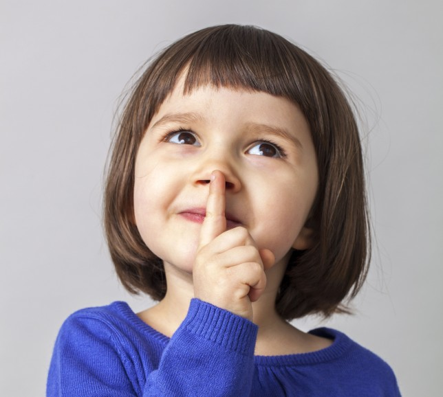 dreamy cute young girl playing with her finger on lips for mystery