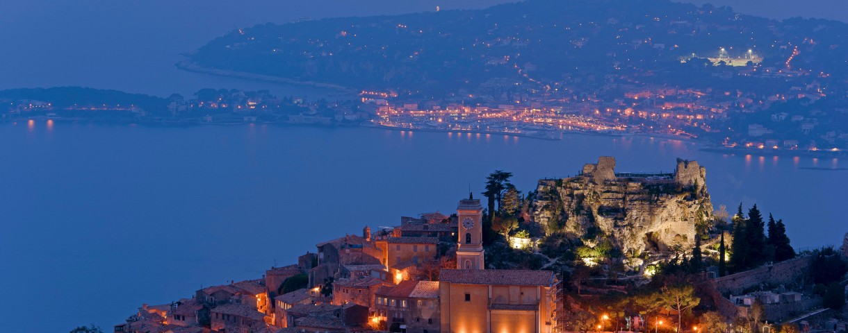 Flood-lit village with church, blue hour, behind coast of the mediterranean sea, Eze, Provence-Alpes-Cote d'Azur, France