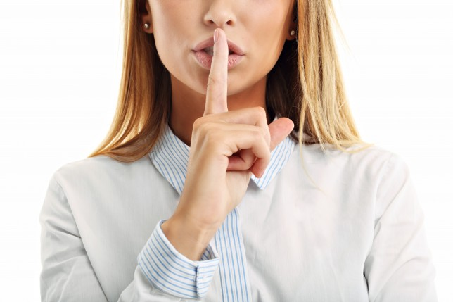 Adult woman holding a finger on her lips over white background